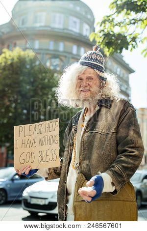 Old jacket. Homeless starving man wearing old brown leather jacket holding sign asking for help poster