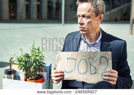 Looking For Employment. Elderly Wrinkled Man Wearing Blue Shirt And Dark Black Suit Holding Sign Whi
