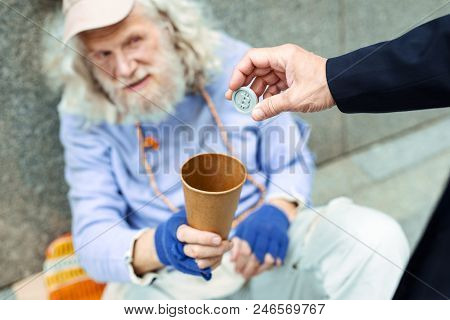 Token For Man. Helpful Supportive Businessman Feeling Sympathetic While Putting Token In Cup For Str