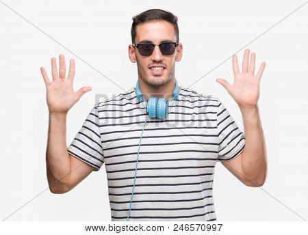 Handsome young man wearing headphones showing and pointing up with fingers number ten while smiling confident and happy.