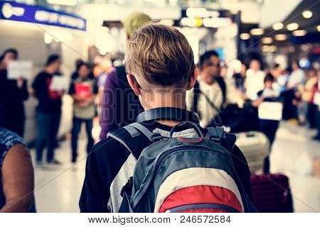Rear view of young caucasian boy walking in the crowded at airport