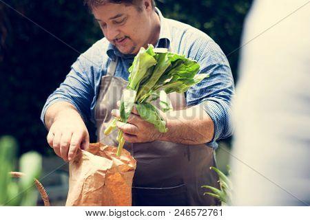 Man buying fresh organic vegetable from market