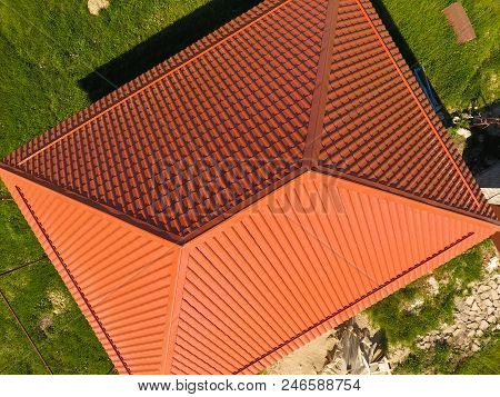 House With An Orange Roof Made Of Metal, Top View. Metallic Profile Painted Corrugated On The Roof
