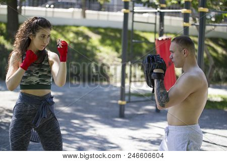 Young Muscular Man And Woman Engaged In Boxing In The Park Ar Sunny Day, Close Up