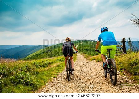 Cycling women and man riding on bikes at  mountains trail landscape. Couple cycling MTB enduro flow track. Outdoor sport activity.