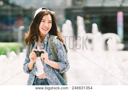 Young Beautiful Asian Backpack Traveler Woman Using Digital Compact Camera And Smile, Looking At Cop