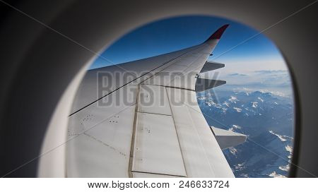 Snow Alps Mountains View In Europe With Airplane Wing Through Aircraft Window