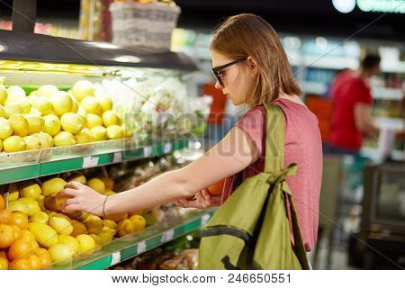 People, Buying Concept. Serious Young Cute Female Comes In Food Store For Buying Fruits, Dressed In
