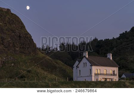 A Image Of A Pretty House On A Moonlit Evening