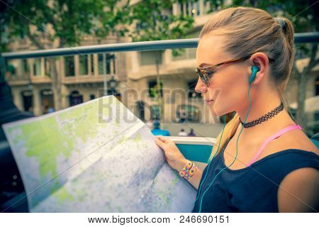 Pretty girl enjoying bus tour in Europe, exploring map and listening stories about famous places of Barcelona, happy active summer vacation, Spain