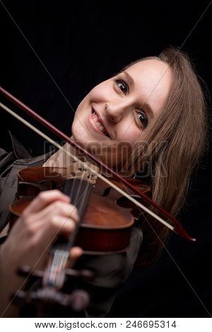 Young Woman With Half Of Her Hair Shaved While Playing A Baroque Violin On A Black Background