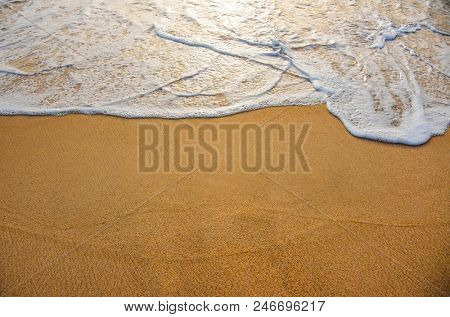 Golden sand with ocean water foam in the sea shore of a beach