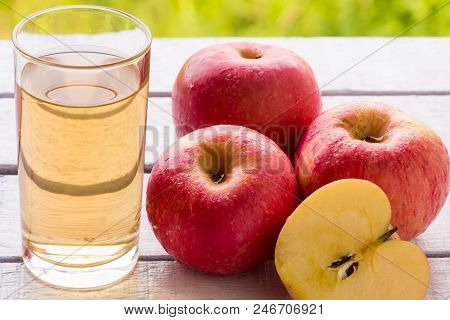 Glass Of Apple Juice And Red Apples On Wooden Table With Natural Green Background