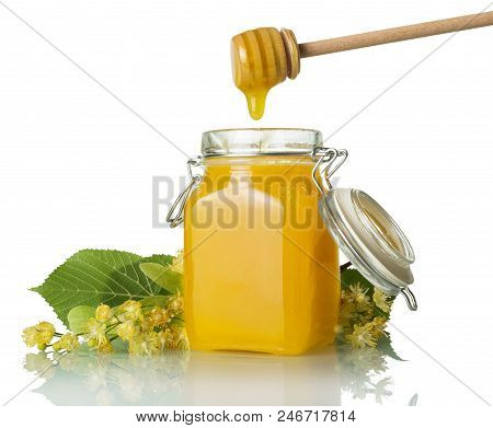 Trickle Of Golden Honey Flows From Beater Into Jar, Isolated On White Background