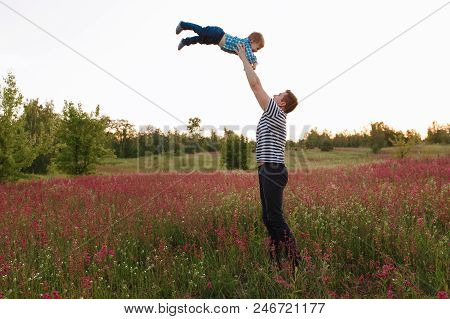 Father And Son Playing In The Spring Field At The Sunset Time. People Having Fun On The Field. Conce