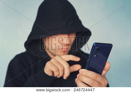Faceless Unrecognizable Hooded Person Using Mobile Phone, Identity Theft And Technology Crime Concep