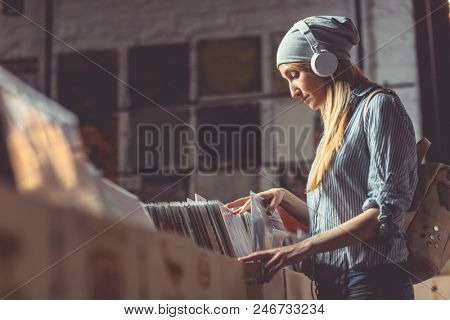 Young woman with headphones browsing vinyl records in a music store