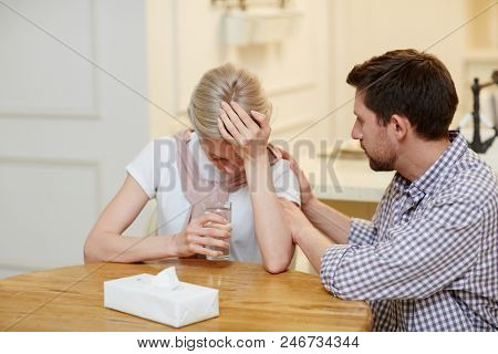 Young sad woman with glass of water leaning over table while hisband comforting her