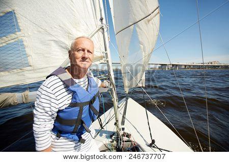 Senior man in lifejacket sitting in yacht and enjoying summer weekend by seaside