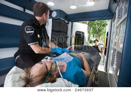 EMT professional check pulse on elderly woman in ambulance
