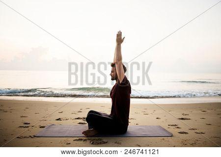 Man practicing yoga on the beach