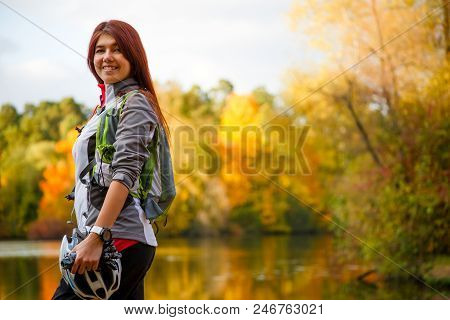 Image Of Smiling Woman With Backpack And Bicycle Helmet Standing Sideways Against Background Of Lake