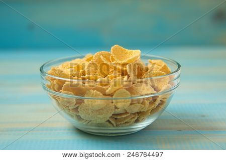 Tasty Cornflakes In Glass Bowl On Blue Background.