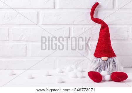 Decorative Christmas Elf Or Gnome On White Wooden Backgroud Against Brick Wall.selective Focus. Plac