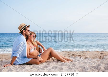 Young Couple In Love Lying On The Beach Enjoying