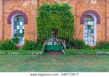 Orange Colored Bricks Stone Wall With Two Big Old Grunge Windows And Closed Grunge Door With Green M