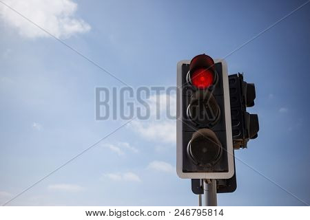 Red traffic light warning the drivers to stop. Blue sky with clouds background. Close up under view, space for text.