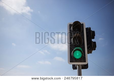 Green traffic light. Signal that it is safe to go on the way. Blue sky with few clouds background. Close up under view, space for text.