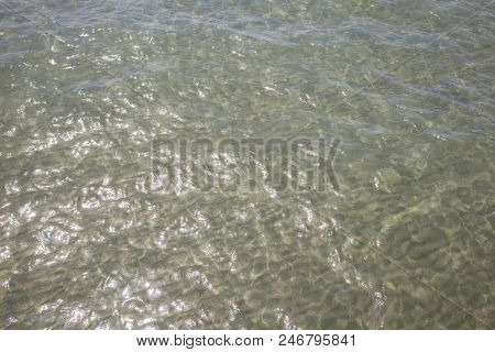 Transparent clear sea at Cyprus island. Crystal water with pebbles and sun's reflection background, above close up view.