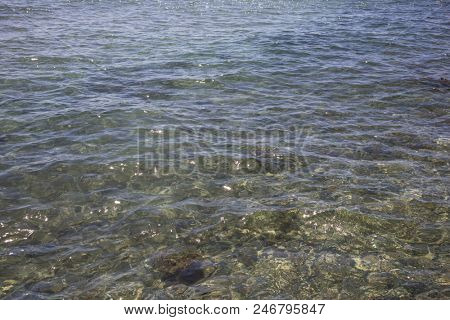 Transparent clear sea at Cyprus island. Crystal water with pebbles and sun's reflection background.