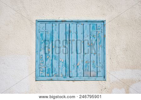 Cyprus, Larnaca. Blue wooden, peeled window, shutters on pink wall. Facade of old stone building, closeup.