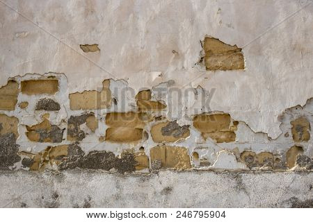 Sandstone, aged stonewall at Cyprus. Pink peeled plaster on yellow limestone wall background, close up view with details.