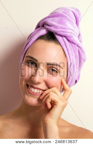 Beauty portrait of a smiling beautiful half naked woman on beauty center wearing pink towel.