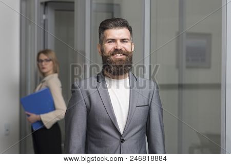 Happy Businessman With Blurred Woman On Background. Bearded Man In Formal Suit In Office. Confident