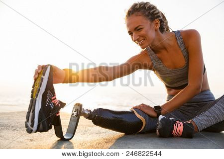 Cropped image of smiling disabled athlete woman with prosthetic leg doing stretching exercises while sitting at the beach