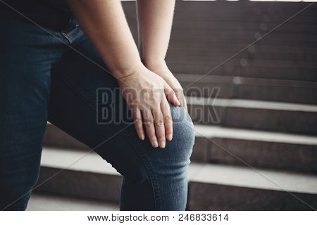 Overweight woman suffering from knee pain stepping on stairs. Excess weight, joint overload, health care and medical concept poster
