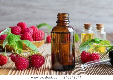 A Bottle Of Raspberry Seed Oil With Fresh Fruit