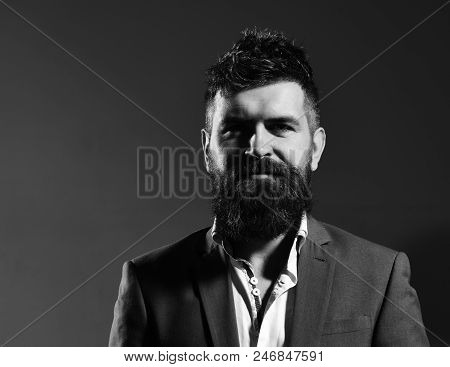 Man In Suit With Intelligent And Confident Face On Black Background. Businessman With Beard And Spik
