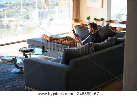 Wide Image Of Good Looking Caucasian Man Lying On A Large Couch In A Modern Living Space In A Gorgeo