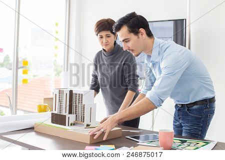 Architect Talking To Building Project Together. Attractive Architect Or Engineer Is Concentrating As