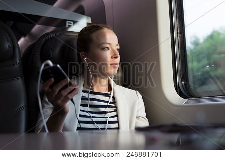 Thoughtful Businesswoman Looking Trough The Window, Listening To Podcast On Cellphone Using Headphon