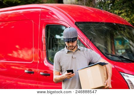 Delivery Man With Cardbox In Hands On The Streets
