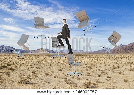 Businessman Climbing Abstract Floating Chairs On Desert Landscape Background. Success And Float Conc