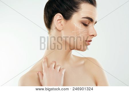 Beautiful Woman   naked shoulders at gray background, beauty photo, close up, antiaging concept, lifting arrows on face. Cosmetology. Skincare. poster