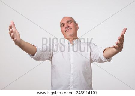 You Are Welcome Concept. Cheerful Mature Man In White Shirt Gesturing Welcome Sign And Smiling While