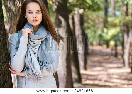Beautiful smiling girl in stylish fashion clothes in autumn Park.  Beautiful woman outdoors in sunny day.